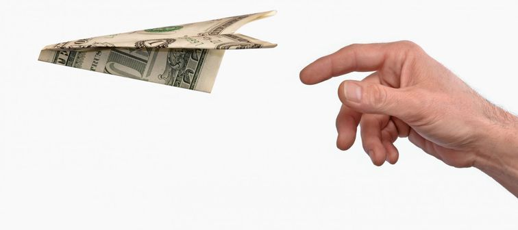 Investment concept.Hand throwing a dollar paper plane isolated on white background.