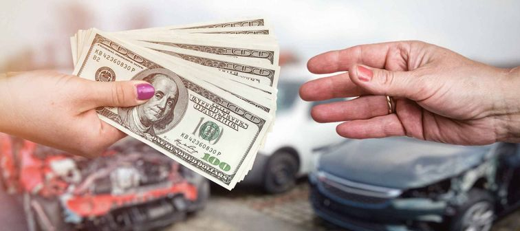 Macro focus on female hands with dollar upon crashed car