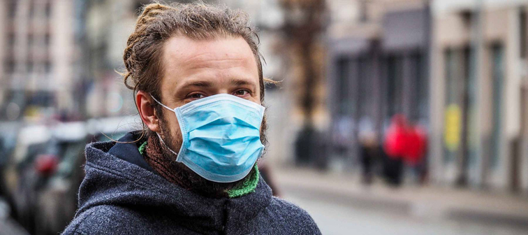 Man on the street wearing face mask to protect against the coronavirus