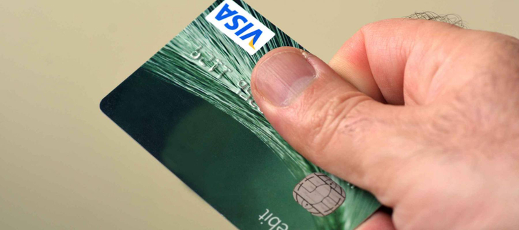 AUCKLAND - SEP 11 2014:Man hands out debit card.Debit cards are the most profitable sector of the American banking industry, with more than $30 billion in profits per year.