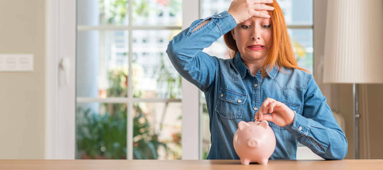 Redhead woman saves money in piggy bank at home stressed with hand on head, shocked with shame and surprise face, angry and frustrated. Fear and upset for mistake.