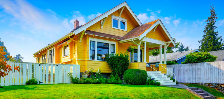 American craftsman home with yellow exterior paint and well kept front garden. Northwest, USA