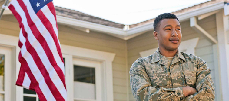Young adult soldier standing with his arms crossed outside his home.