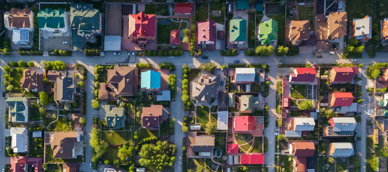 Aerial photography of a a cottage village with colorful houses, a good road, green trees and yards. Helicopter drone shot