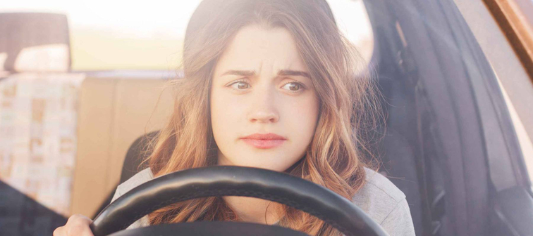 Nervous young woman, a first-time driver, sits at the wheel of a car