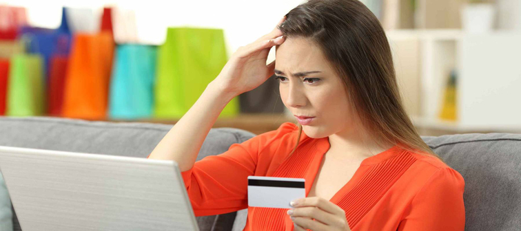 Worried shopper buying online with credit card sitting on a couch in the living room at home