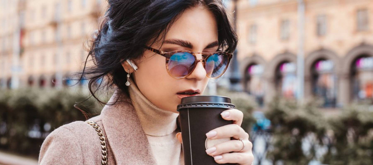 Woman with dark hair and sunglasses walking outdoors with takeout coffee