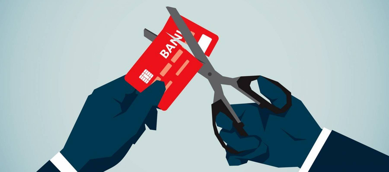 Illustration of one hand holding a red credit card while the other cuts it with scissors