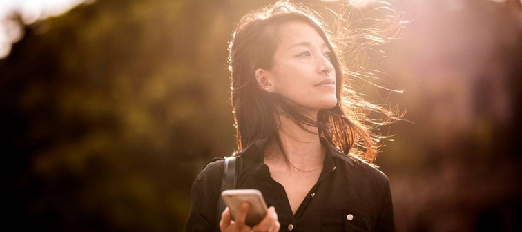 Young Asian-American woman holding cellphone in the sun