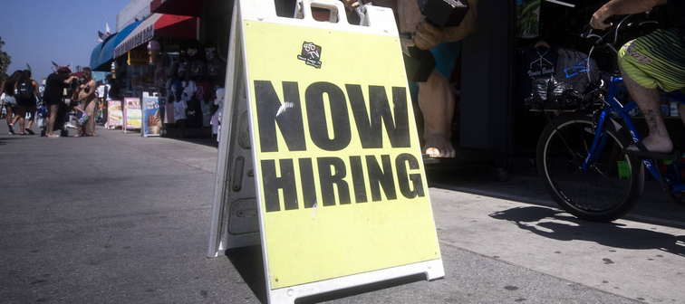 A sign on the walkway next to a shop reads 'Now Hiring' close to the beach amid the coronavirus pandemic in Venice Beach, California, Sept. 5, 2020.