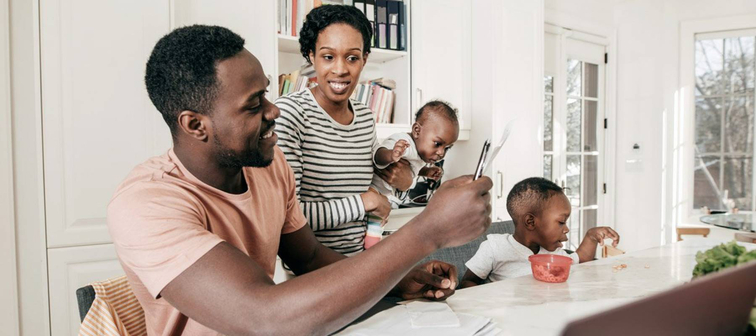 African-American couple with two children working on their finances at their dining table
