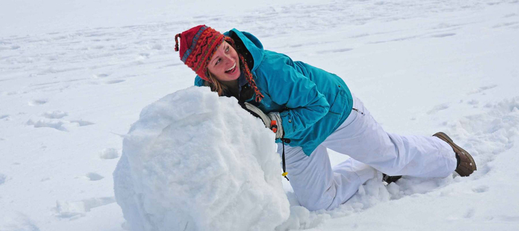 Young college-age woman rolling giant snowball to make snowman