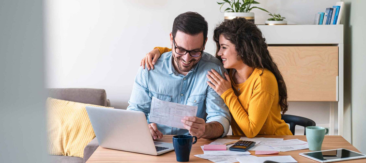 Positive young couple embracing and paying household bills or taxes on laptop online at home stock photo