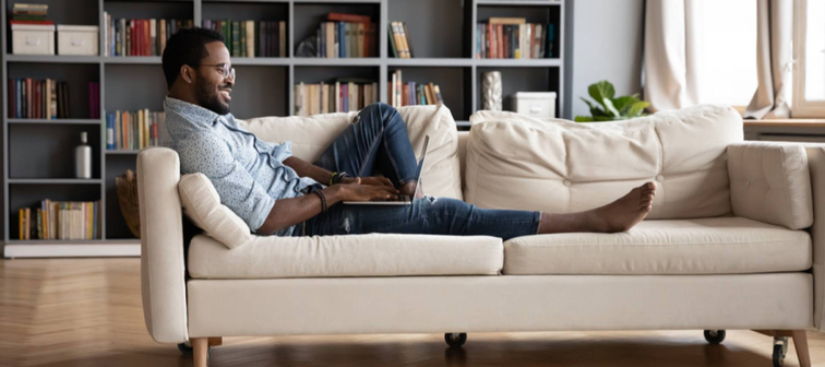 African-American man sits barefoot on a sofa typing on a laptop