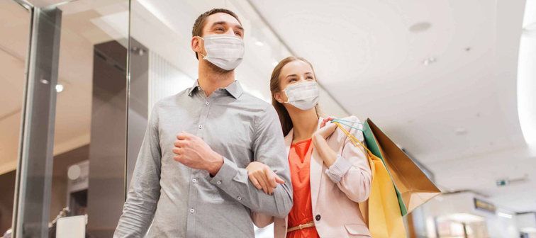 sale, consumerism and pandemic concept - happy young couple wearing face protective medical mask for protection from virus disease with shopping bags in mall