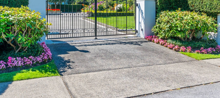 Metal gates with driveway to the luxury house.  North America.