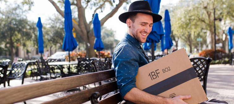 Hipster wearing a wide-brimmed hat sitting on a park bench holding a box from Amazon