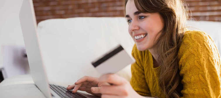 Young woman using her credit card to buy online sitting on the couch at home