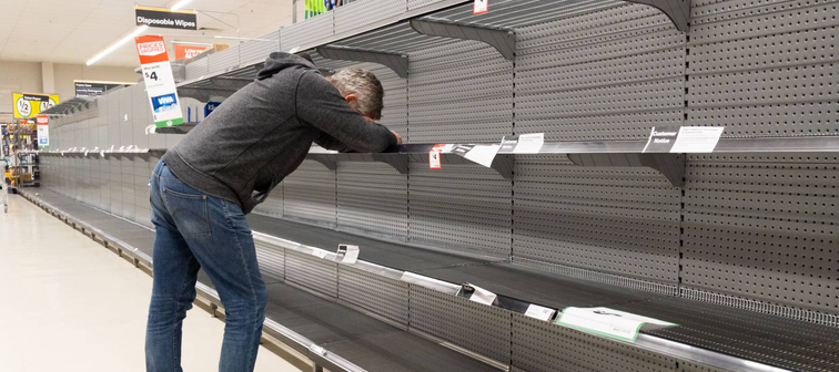 Man stands in supermarket aisle frustrated by empty shelves