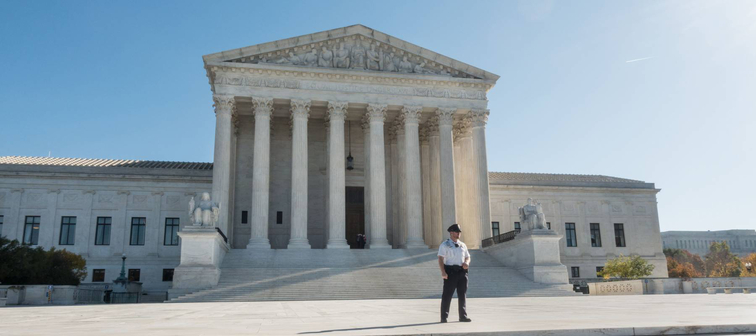 A guard keeps protesters away from the U.S. Supreme Court during arguments on the Affordable Care Act, Nov. 10, 2020.