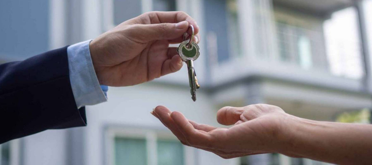 man in suit hands over keys to open hand