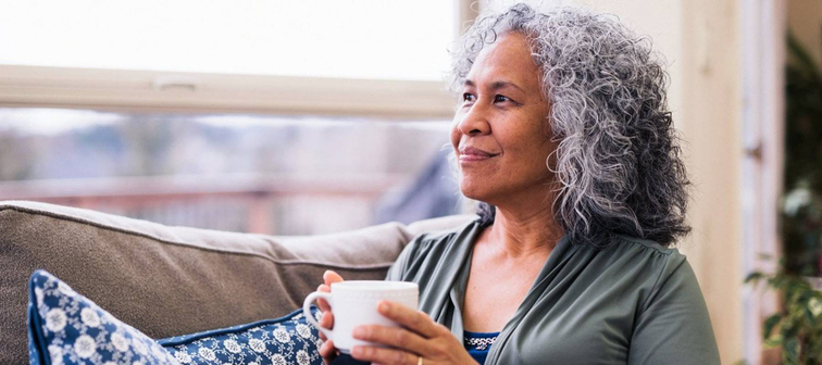 Senior woman holding coffee mug sitting on couch looking out window