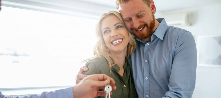 Happy couple handed keys to new house
