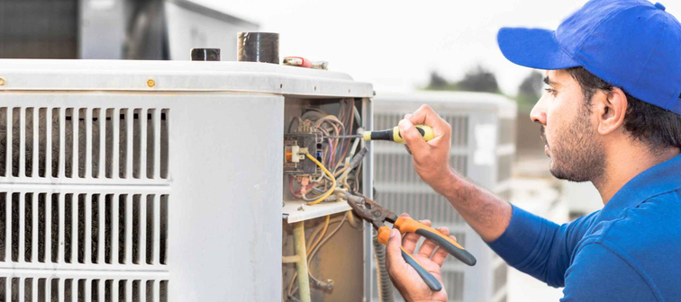 a contractor works on an air conditioning system with tools