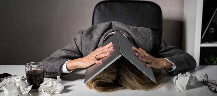 Frustrated woman hiding under laptop in office
