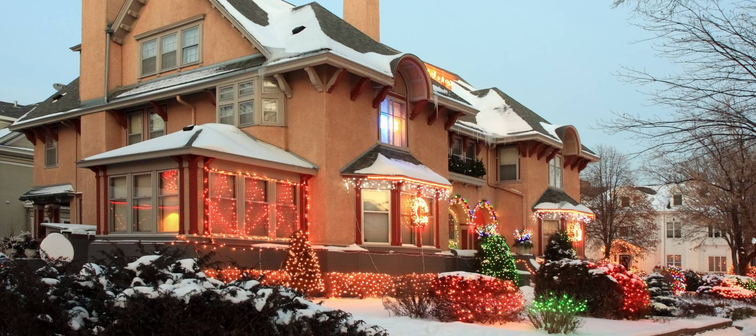Outside of house covered by snow decorated with Christmas lights