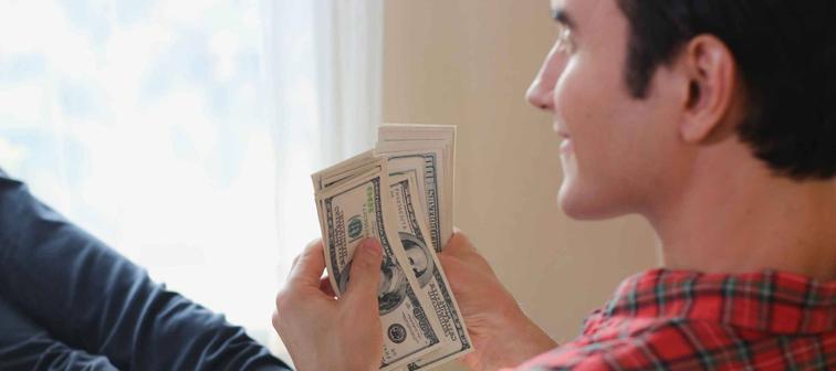 Uomo visto da dietro, allungando le gambe, appoggiandosi allo schienale della sedia, contando le banconote da un dollaro