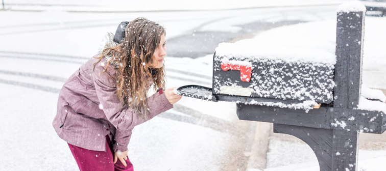 girl looks into mailbox in the snow