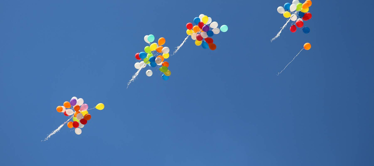 Bouquets of balloons rising against a blue sky.
