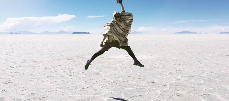 A man is jumping up on the dazzling Uyuni Salt Flat in Bolivia - the one of the travel destinations.