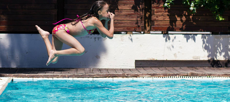 Young teenage girl jumping into pool