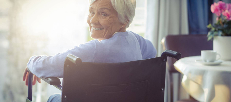 Portrait of smiling senior woman senior woman sitting on wheelchair at home
