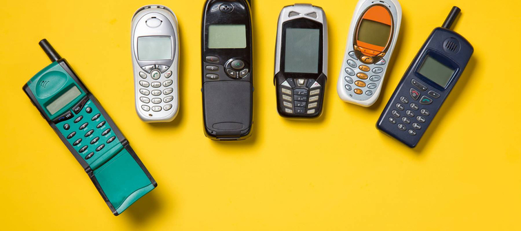 Old mobile phones on yellow background