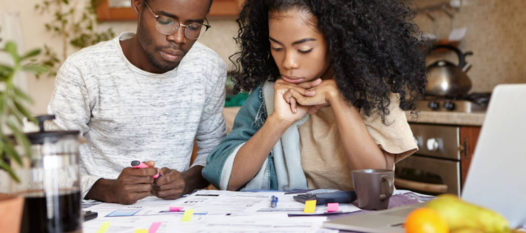 Young African couple doing paperwork together, sitting at kitchen table with lots of papers, calculator and laptop, looking frustrated. Dark-skinned family calculating domestic budget at home