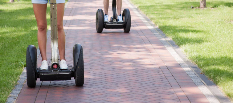 Portrait of beautiful young woman and handsome man. Girl and boy using segway. Girl smiling. Green alley as background