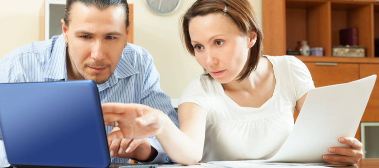 Positive couple with financial documents and laptop at table in home interior