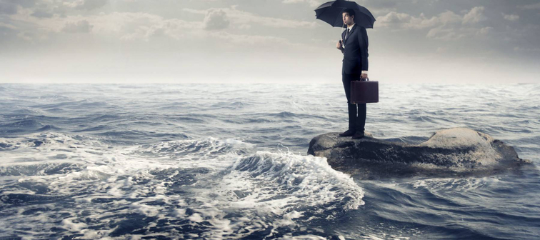 Businessman under an umbrella standing on a rock in the middle of a slight sea