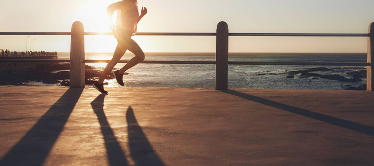 Side view of fitness woman running on a road by the sea. Sportswoman training on seaside promenade at sunset.