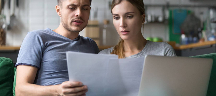 Serious confused couple checking high domestic bills with papers and laptop