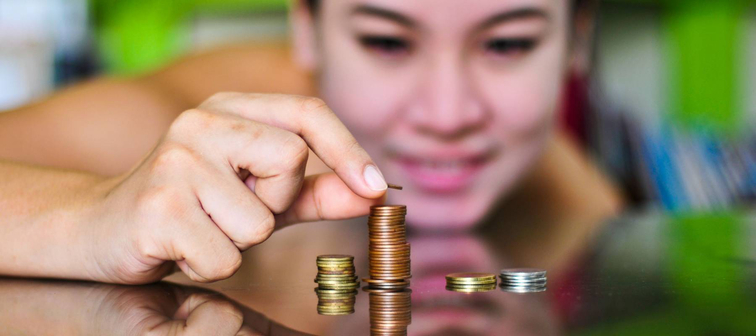 Asian girl collecting coins to save.
