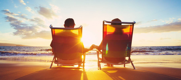 Retired couple enjoying beautiful sunset at the beach