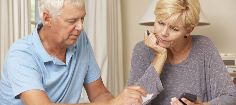 Worried Mature Couple Checking Finances And Going Through Bills Together