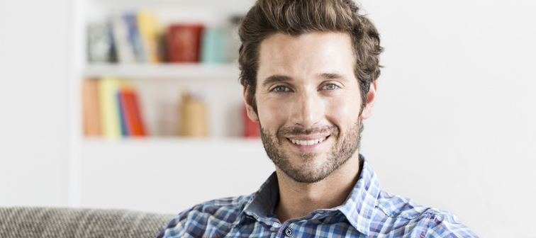 Cheerful bearded 30 year old man portrait in modern house