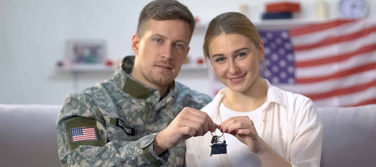 American male soldier and his wife holding house key reward for military service