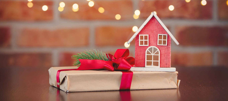 Christmas gift box and wooden toy house on background with fairy lights in bokeh. Holiday season