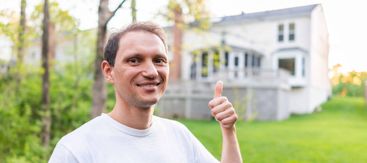 Young man happy homeowner in Herndon, Northern Virginia, Fairfax county residential neighborhood in spring or summer house backyard pointing with thumb